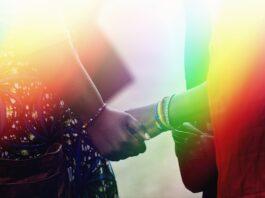 Dos personas dándose la mano con los colores del arcoíris superpuestos (Depto. de Estado de EE. UU.)