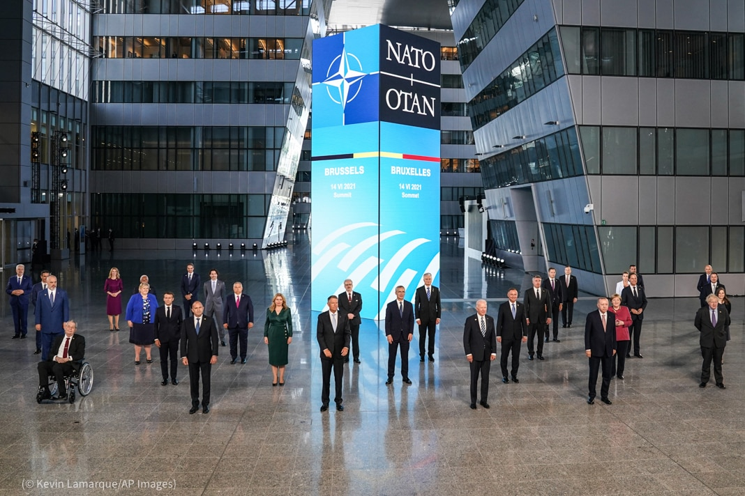 =Men and women standing in large atrium with space between them in front of large NATO sign (© Kevin Lamarque/AP ImagesMen and women standing in large atrium with space between them (© Kevin Lamarque/AP Images)