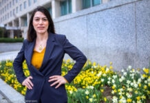 Une femme, les mains sur les hanches, debout devant un bâtiment (Département d'État/D.A. Peterson)