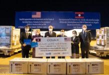 زنان و مردان در کنار جعبه های واکسن های اهدایی با نشان کوواکس ایستاده اند. (U.S. Government)