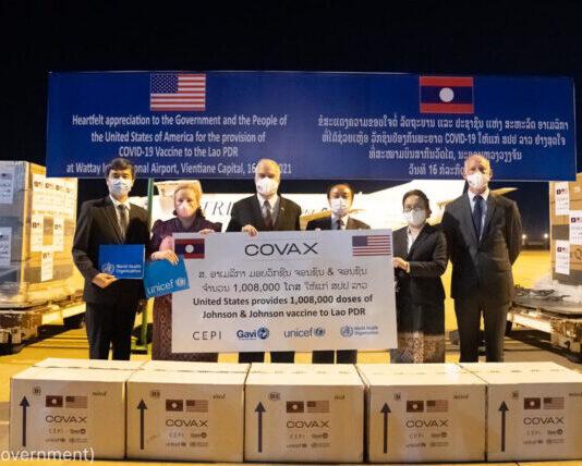 Группа людей на фоне ящиков с вакцинами против COVID-19, поставленными по программе COVAX (U.S. Government)