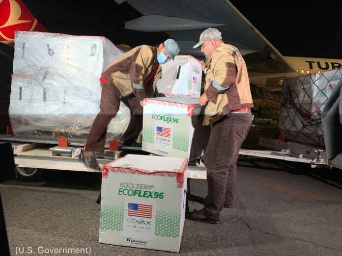 Men unloading boxes from plane (U.S. Government)