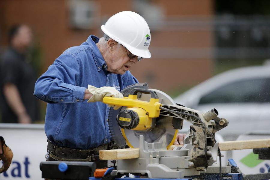 2015年11月25日卡特在建筑工地做义工切割木材(照片:美联社)