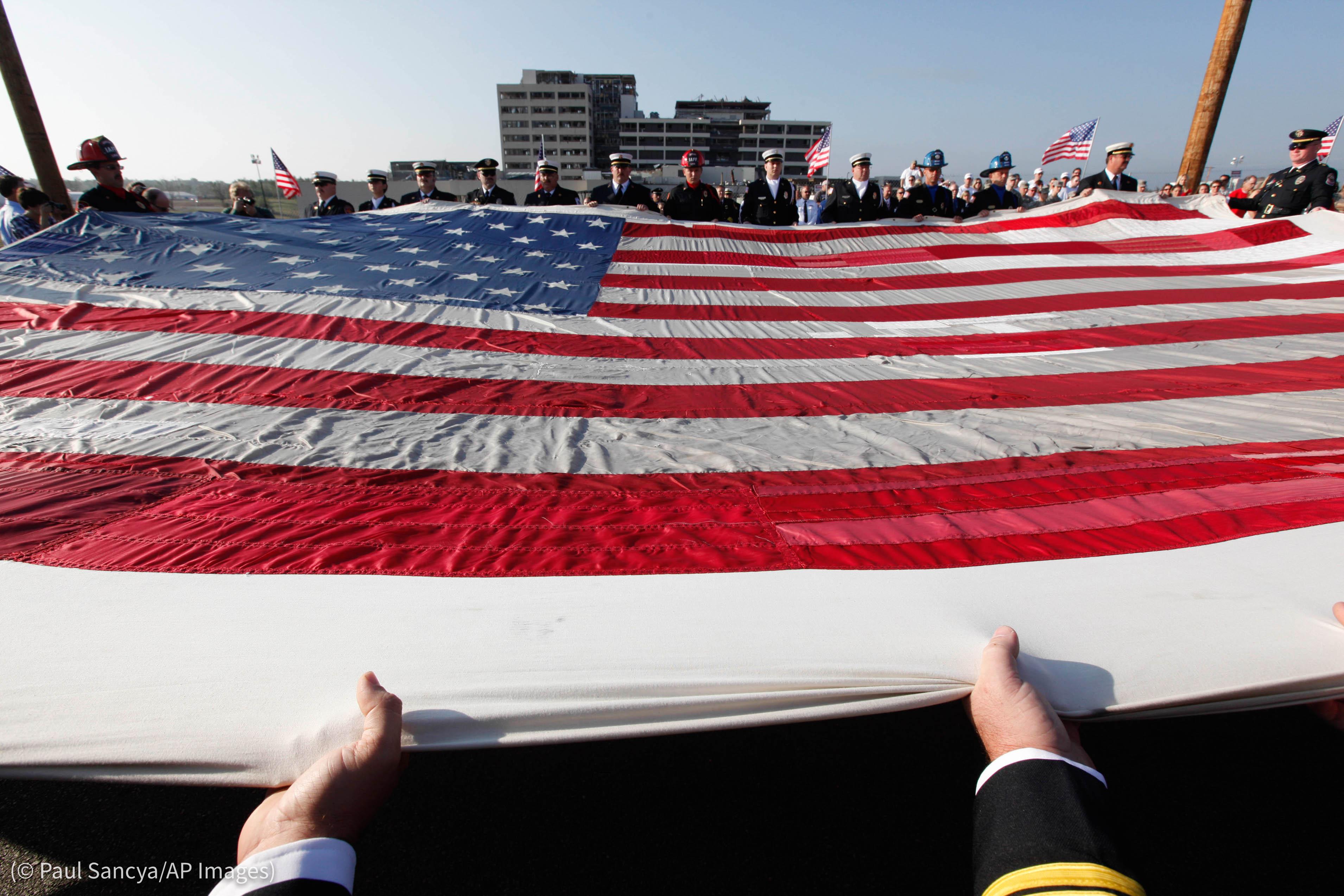 People in various uniforms holding large American flag (© Paul Sancya/AP Images)