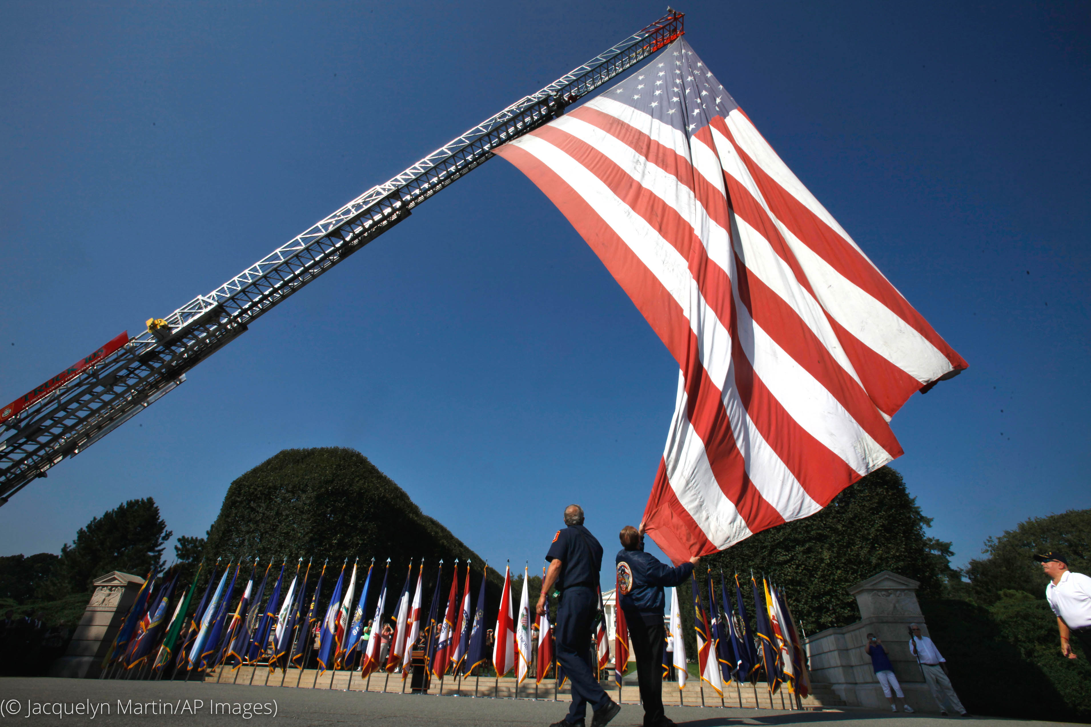 Uniformed person holding edge of large American flag being flown from fire truck ladder (© Jacquelyn Martin/AP Images)