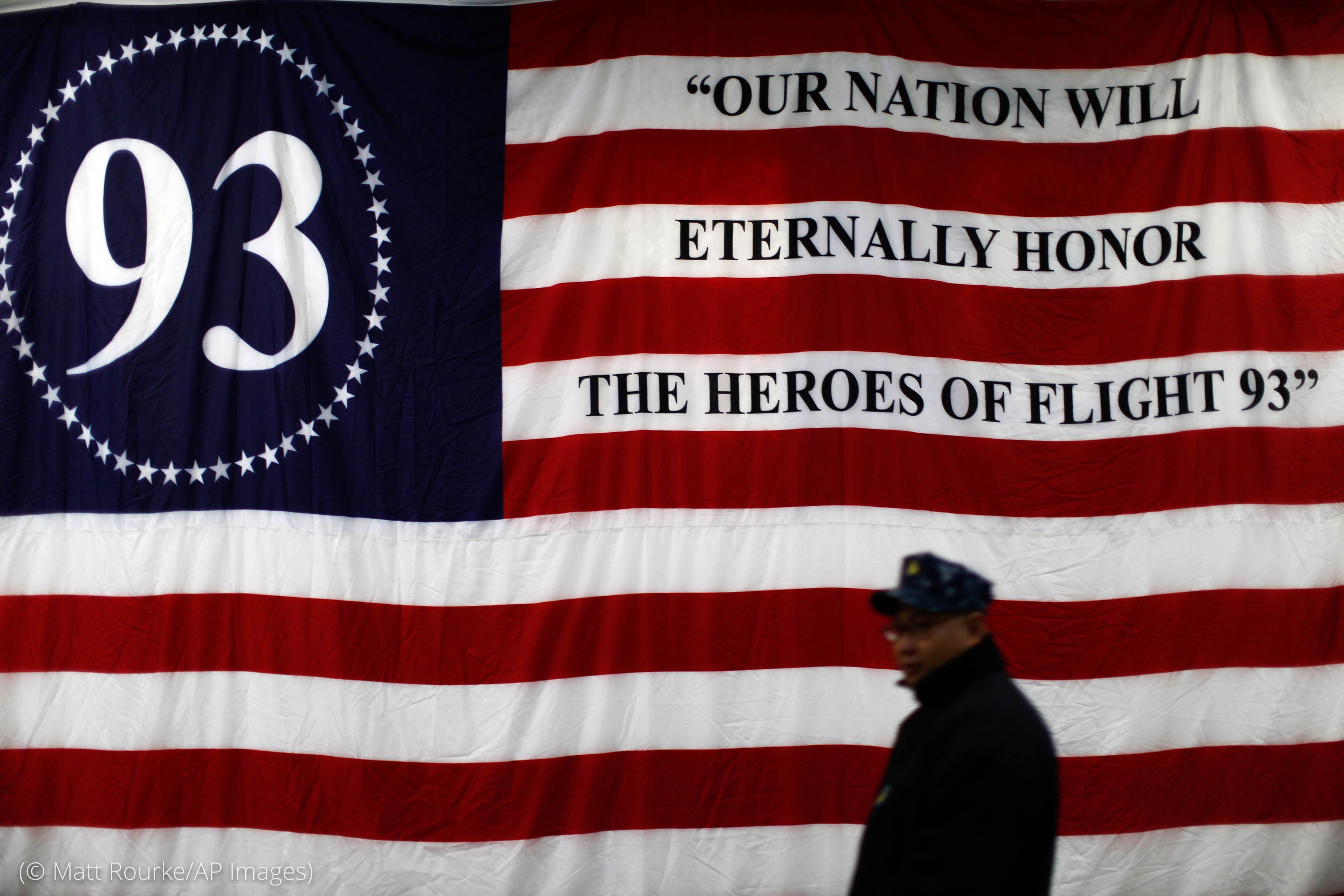 Sailor walking past large red, white and blue flag commemorating United Flight 93 (© Matt Rourke)