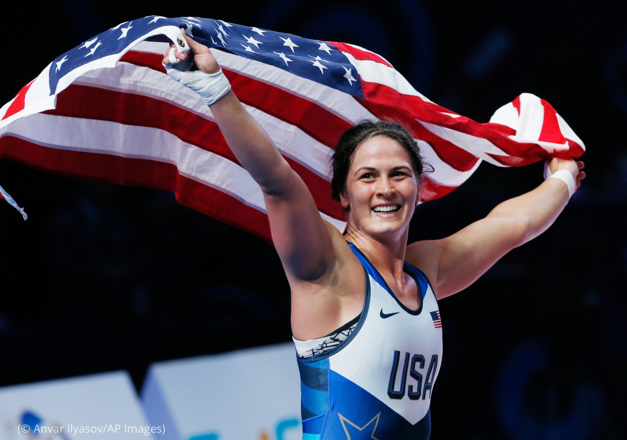 Mujer sonriendo y sosteniendo la bandera de Estados Unidos (© Anvar Ilyasov/AP Images)