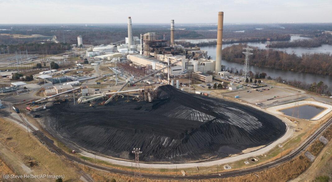 河边一座发电厂附近的大片储煤场(© Steve Helber/AP Images)