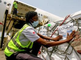 Un hombre coloca un cartel en un palé de cajas con vacunas contra COVID-19 (© Diomande Ble Blonde/AP Images)
