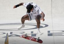 Nyjah Huston in midair with inverted skateboard in rink (© Alessandra Tarantino/AP Images)