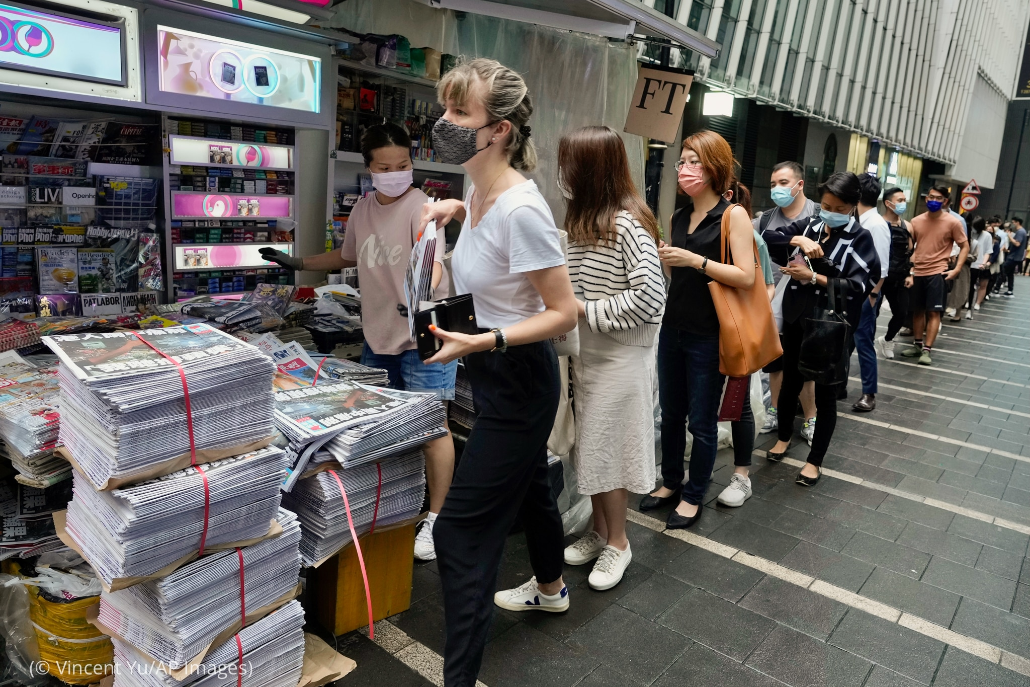 People standing in long line to newspaper stand (© Vincent Yu/AP Images)