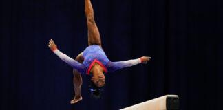 Simone Biles fazendo salto mortal em uma barra de equilíbrio (© Jeff Roberson/AP Images)