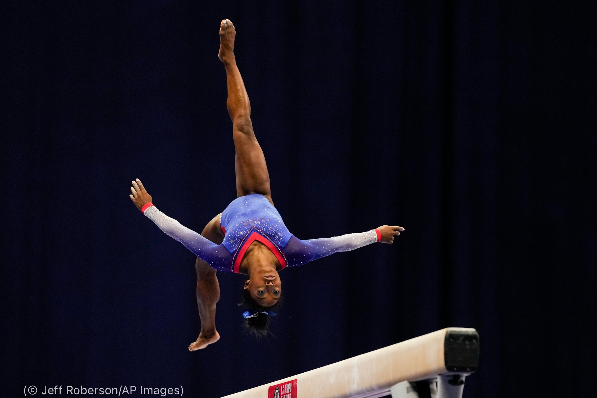 Simone Biles dando vueltas en el aire sobre la barra de equilibrio (© Jeff Roberson/AP Images)