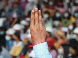 Persona haciendo el saludo de los tres dedos, multitud al fondo (© AP Images)