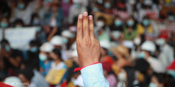 Person making three-fingered salute, crowd in background (© AP Images)