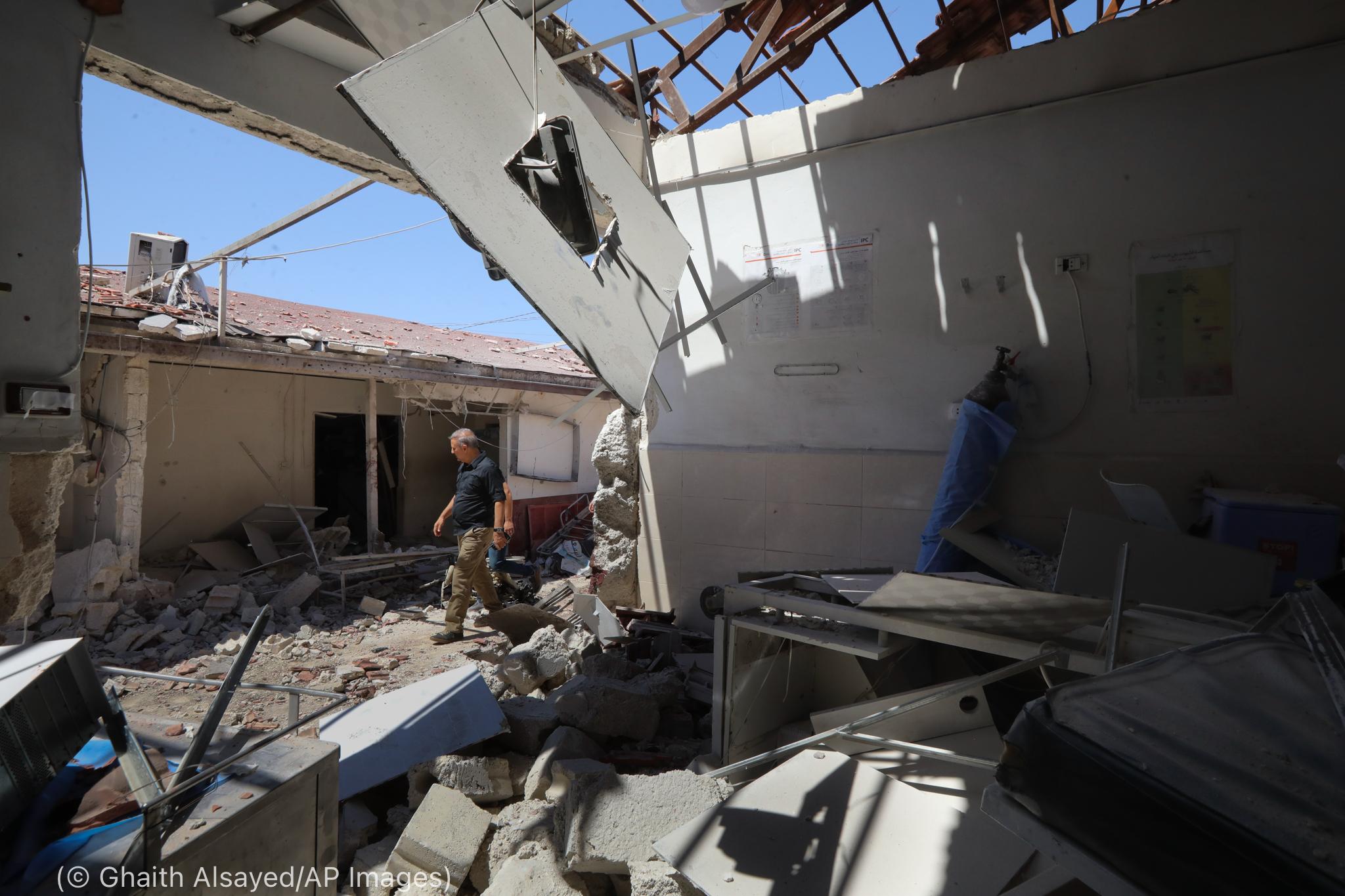 Un homme marchant dans les décombres d'un hôpital détruit (© Ghaith Alsayed/AP Images)