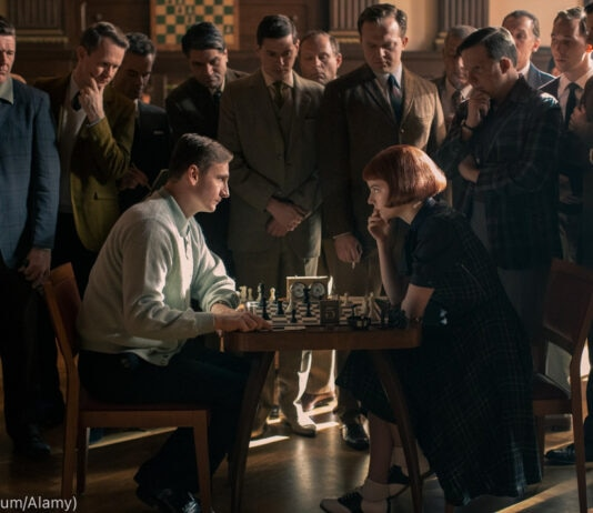 Dua orang sedang duduk bermain catur dengan sekelompok orang berdiri menonton (© Album/Alamy)