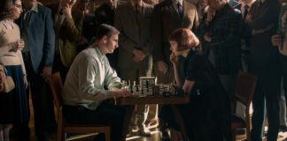 Dos personas jugando al ajedrez mientras un grupo de personas sentadas observan (© Album/Alamy)