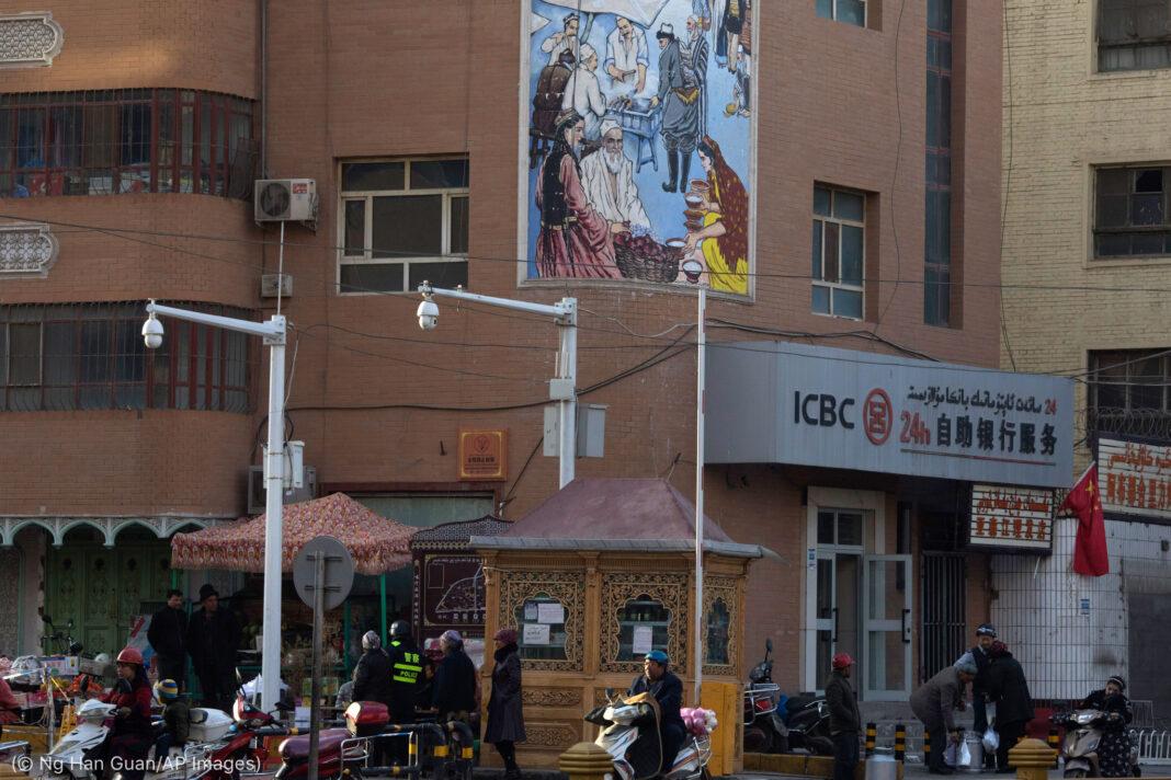Жители города идут мимо вывесок и камер видеонаблюдения (© Ng Han Guan/AP Images)