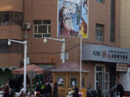 People in an urban area with commercial signs and security cameras (© Ng Han Guan/AP Images)