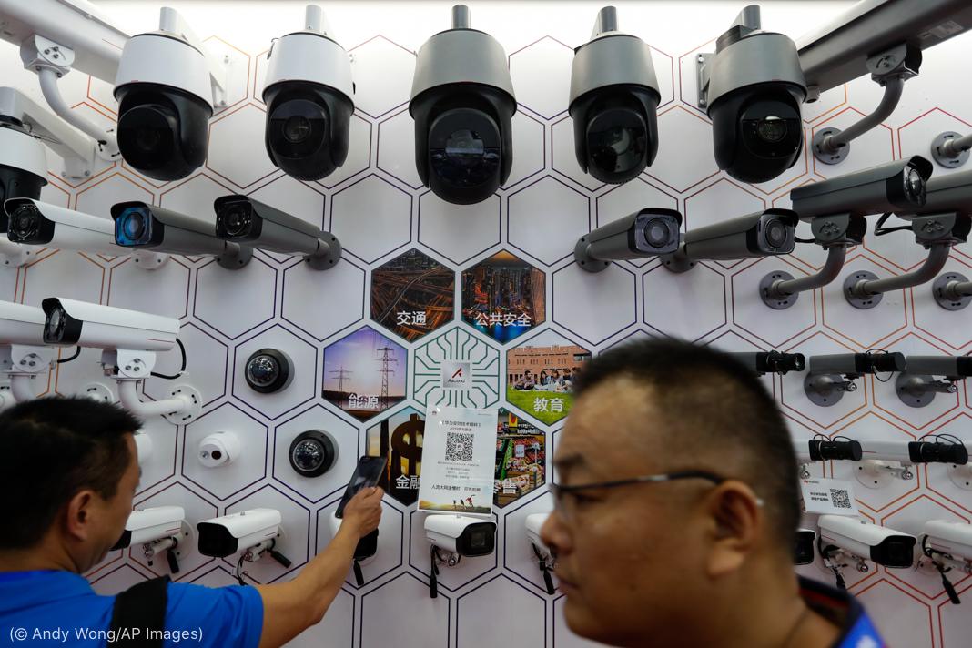 Люди смотрят и проходят мимо камер наблюдения, выставленных на выставке (© Andy Wong/AP Images)