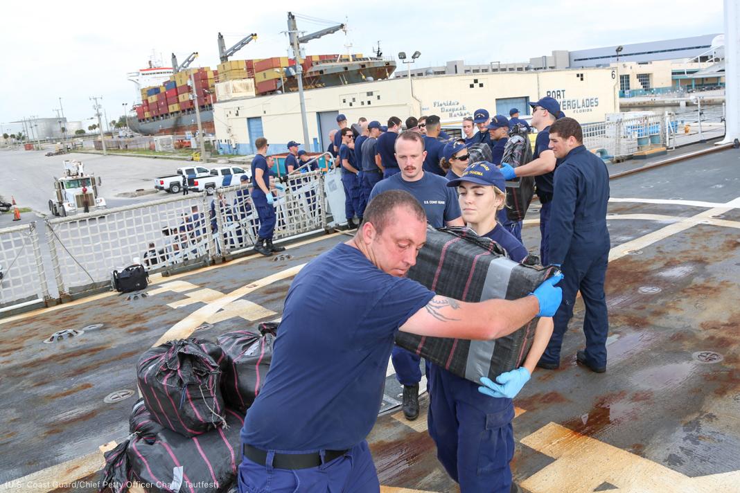 Miembros de la Guardia Costera de EE. UU. en uniforme descargando paquetes en un puerto (U.S. Coast Guard/Oficial jefe Charly Tautfest)
