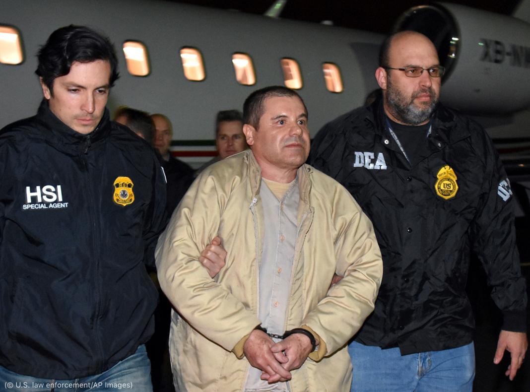 """Dos hombres con chaquetas de las fuerzas del orden custodian a Joaquín """"El Chapo"""" Guzmán cerca de un avión en una pista (© U.S. law enforcement/AP Images)"""