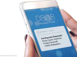 Tangan memegang ponsel yang menampilkan peringatan ShakeAlert (U.S. Geological Survey, Department of the Interior)