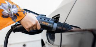 Mão de uma mulher conectando um cabo de carregamento em um veículo elétrico (© Santiago Mejia/The San Francisco Chronicle/Getty Images)