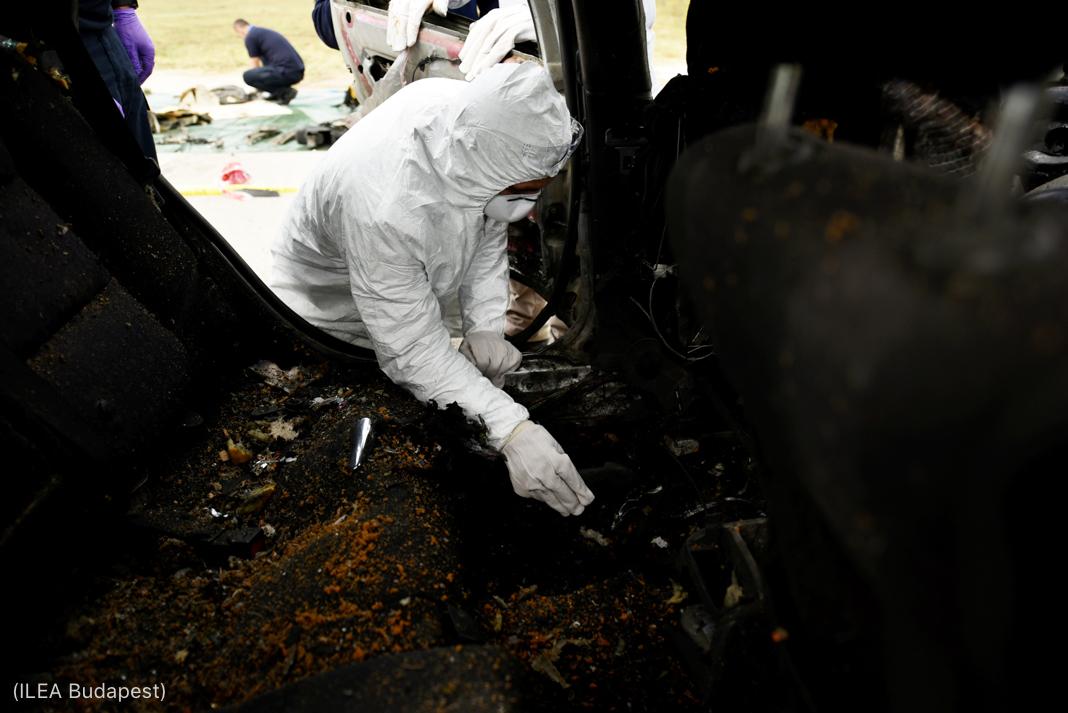 Persona con traje de protección blanco, mascarilla y guantes rebuscando entre escombros de un auto tras la explosión de una bomba (ILEA Budapest)