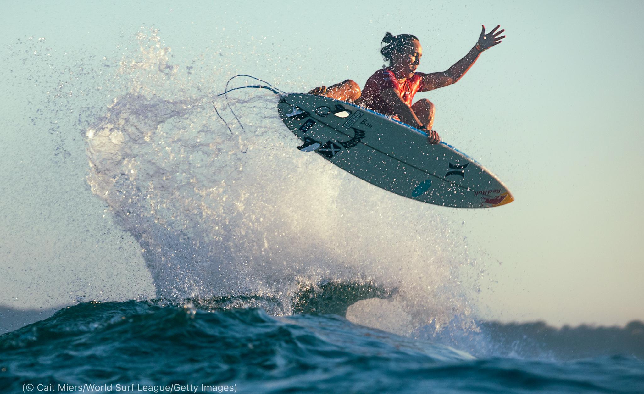 Mujer suspendida en el aire sobre una ola en una tabla de surf (© Cait Miers/World Surf League/Getty Images)