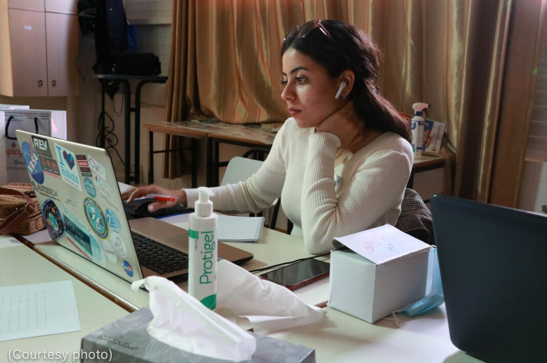 Une femme assise devant un ordinateur portable (Photo offerte)