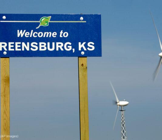 Papan 'Selamat datang di Greensburg, Kansas,' di sebelah dua turbin angin (© Charlie Riedel/AP Images)