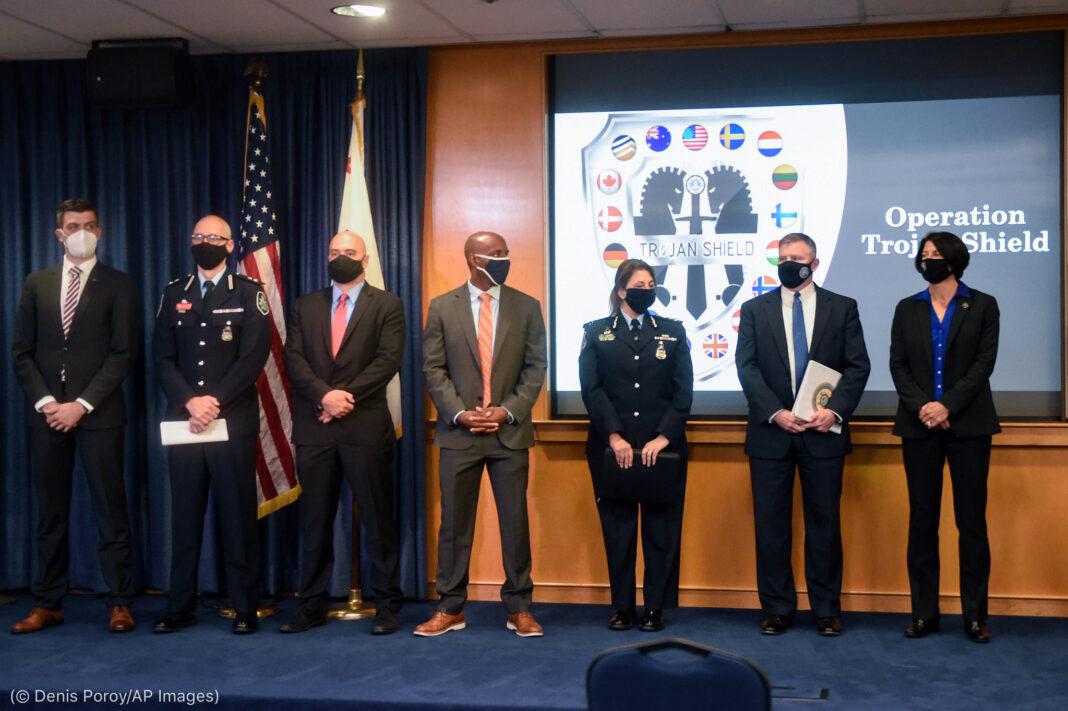 """Funcionarios con mascarillas frente a dos banderas y el logotipo de la operación """"Escudo de Troya"""" proyectado en pantalla (Denis Poroy/AP Images)"""