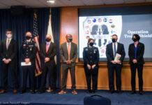 Para pejabat mengenakan masker berdiri di depan dua bendera dan logo Operation Trojan Shield yang diproyeksikan di layar ( Denis Poroy/AP Images)