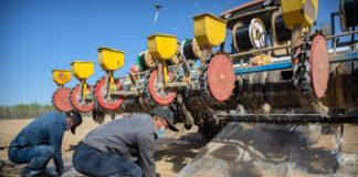 Мужчины привязывают пластиковые парусы рядом с сельскохозяйственным оборудованием в поле (© Mark Schiefelbein/AP Images)