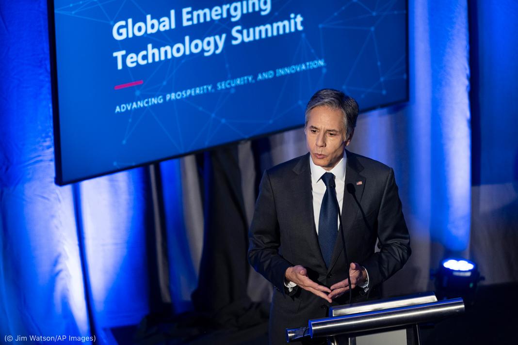 """Antony Blinken falando na frente de telão no qual estão projetadas as palavras """"Cúpula Global de Tecnologia Emergente"""" (© Jim Watson/AP Images)"""