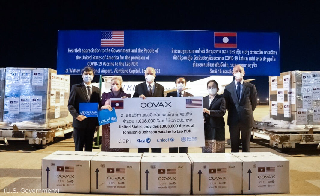 Officials posing with COVID-19 vaccine boxes on tarmac (U.S. Government)