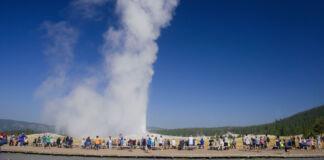 Grupo de pessoas observando gêiser em erupção (© Dave Stamboulis/Alamy)