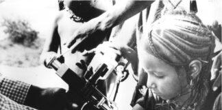 একটি শিশুর বাহুতে টিকার ধাতব যন্ত্র ধরে আছে বয়স্ক মানুষের হাত। (ইউএসএআইডি)