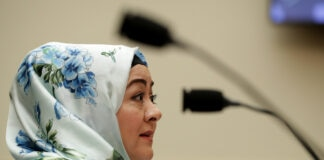 Perempuan mengenakan jilbab berbicara ke mikrofon (© Chip Somodevilla/Getty Images)