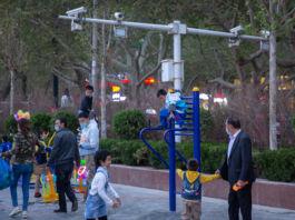 Des enfants et des adultes sur un terrain de jeux sous des caméras de sécurité (© Mark Schiefelbein/AP Images)