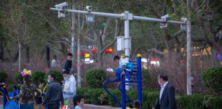Niños y adultos en un parque infantil cerca de cámaras de seguridad (© Mark Schiefelbein/AP Images)