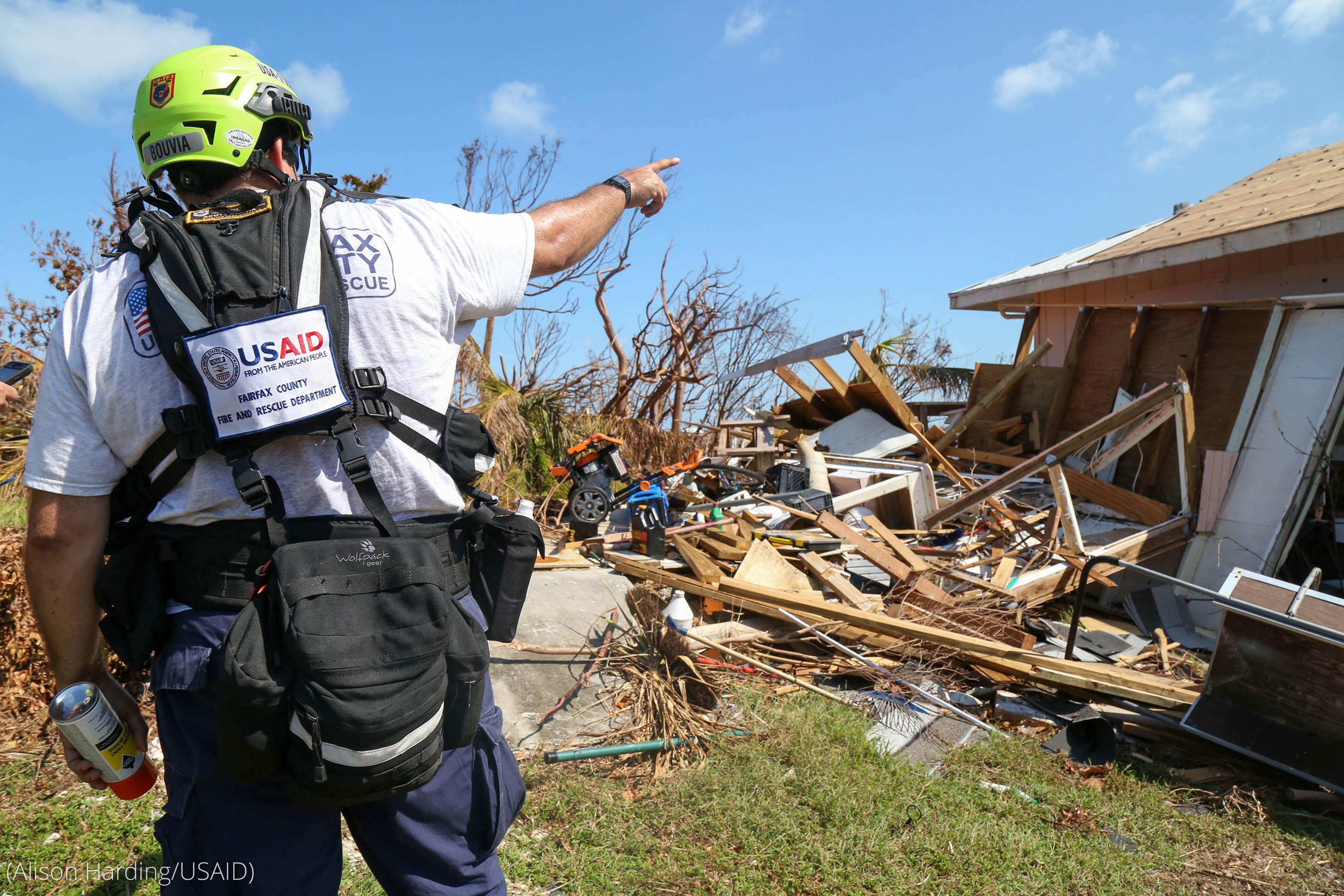 Мужчина в защитном шлеме на ремне крупного оборудования указывает на обломки разрушенного дома (Alison Harding/USAID)