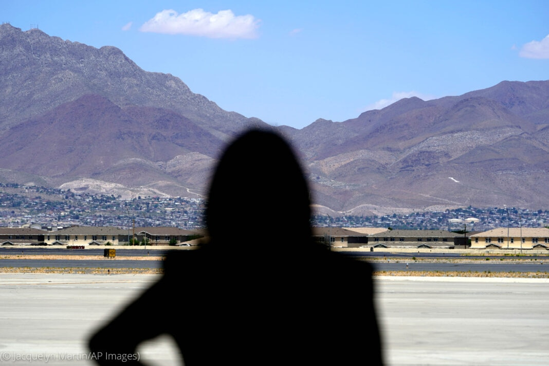 The back of Vice President Harris standing in front of mountains (© Jacquelyn Martin/AP Images)