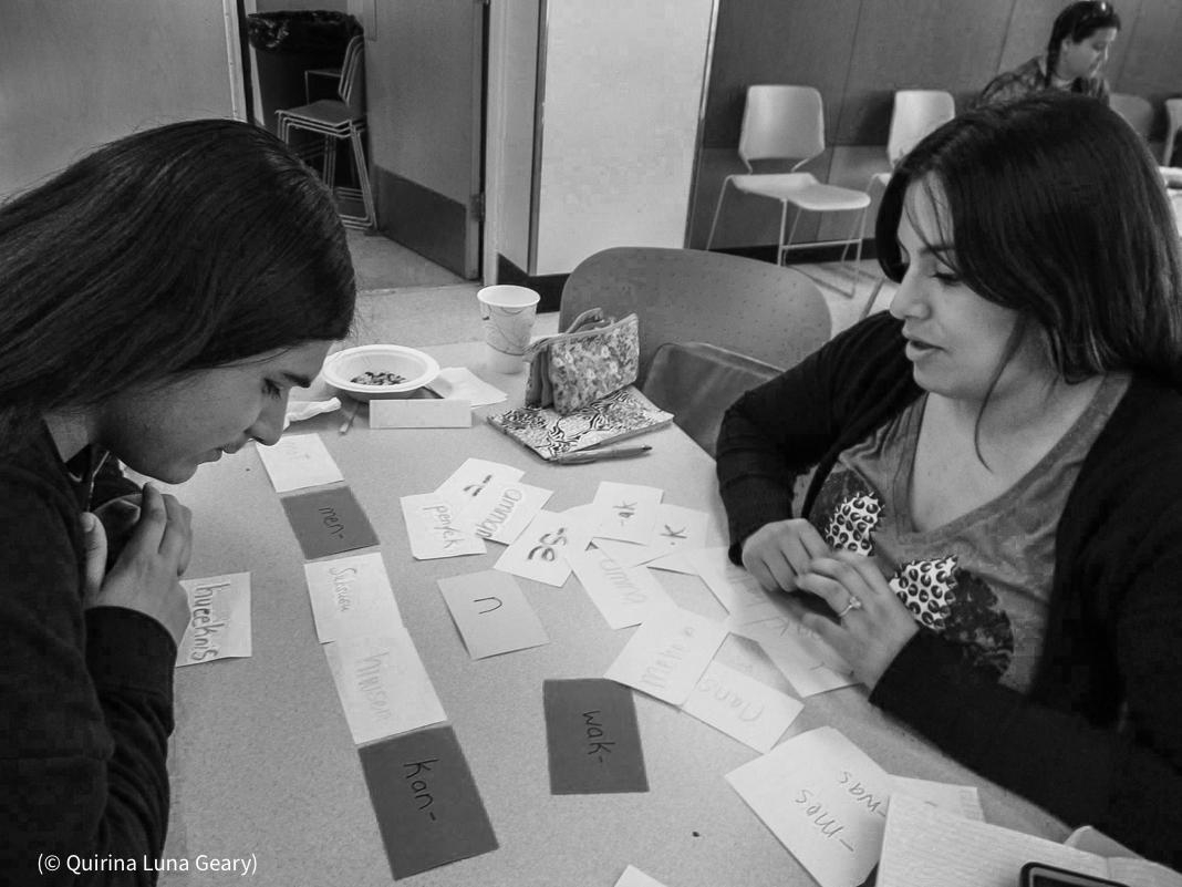 চেয়ারে বসা দুজন টেবিলের ওপর রাখা কার্ডগুলো দেখছেন (©কিরিনা লুনা গিয়ারি)