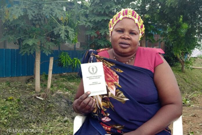 Una mujer sostiene tarjeta de vacunación (© UNICEF/Mach)