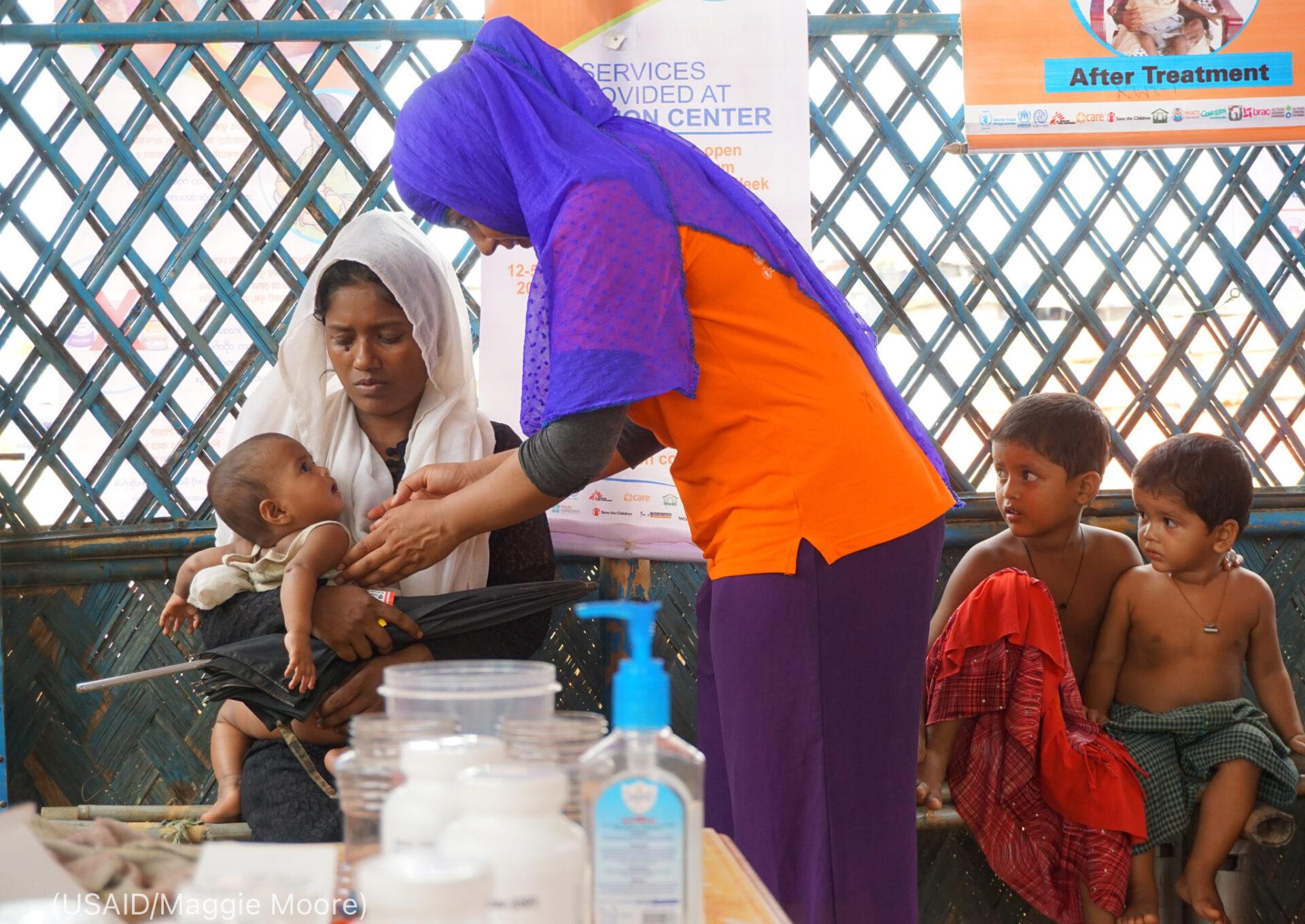 Perempuan menggendong bayi untuk diperiksa oleh perempuan lainnya sementara dua anak lainnya menyaksikan (USAID/Maggie Moore)