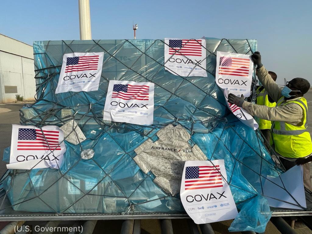 Homem coloca adesivo com a bandeira dos EUA e 'Covax' em caixas sobre estrados (Governo dos EUA)