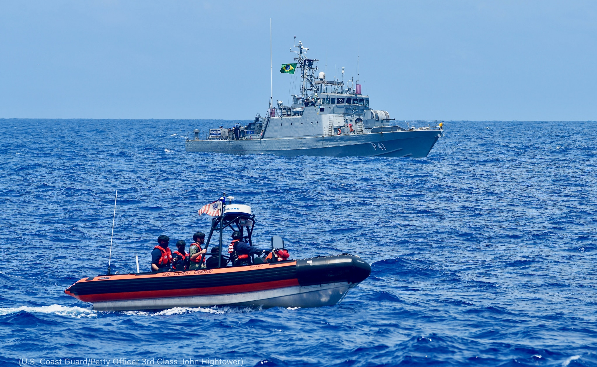 Small boat in front of navy ship during joint maneuvers (U.S. Coast Guard/Petty Officer 3rd Class John Hightower)